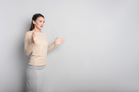 pleasant emotions: Express emotions. Pleasant beautiful young woman holding her hands in front of her body and expressing surprise while standing against grey background Stock Photo