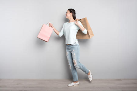 Happy after shopping. Positive delighted woman holding packages and going resting after visiting shops while expressing positivity Stock Photo