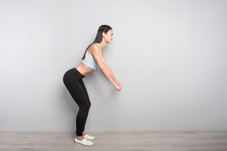 activate: Activate your muscles. Joyful delighted woman smiling and doing sport exercises while standing isolated on grey background