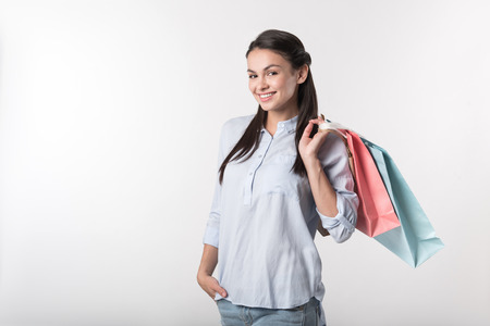relieve: Best way to relieve stress. Cheerful delighted woman holding packages behind her shoulder and smiling while resting after shopping
