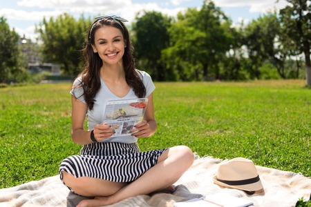 In a good mood. Positive beautiful young woman using tablet and sitting on the grass while enjoying nature