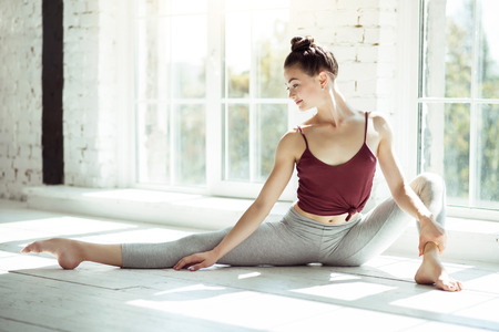 Keep training. Young beautiful smiling girl wearing a sportswear while doing her stretching exercises having a split. Фото со стока
