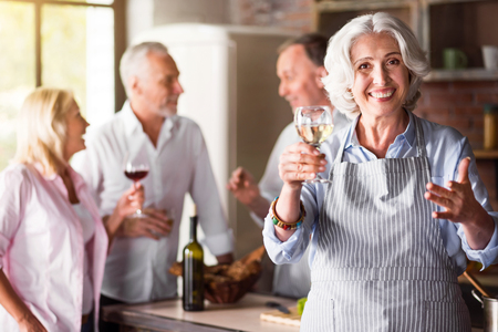offsprings: I love them. Happy elderly elegant woman smiling in the kitchen while having a drink and enjoying celebration with her family.