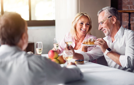 offsprings: Delicious meal together. Happy smiling woman enjoying the dish with her elderly father while celebrating and sitting in their kitchen.