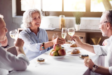 offsprings: For your health. Smiling pleasant elderly woman drinking champagne with her lovely husband and enjoying the time with her family while dining. Stock Photo