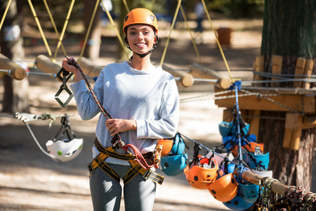 think safety: Think about your safety. Pleasant delighted positive woman holding a mountain carabiner and smiling while standing in the rope park