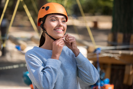 elated: Necessary thing. Beautiful elated young woman smiling and wearing a helmet while getting ready to climb