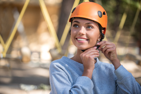 Pleasant anticipation. Attractive cheerful exited woman smiling and wearing her helmet while preparing to enjoy an adventure in the rope park
