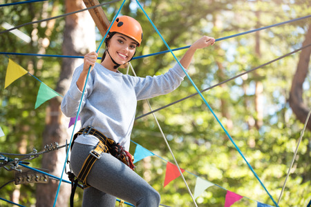 Interesting activity. Good looking delighted enthusiastic woman standing high above the ground and smiling while following her rope route Banque d'images