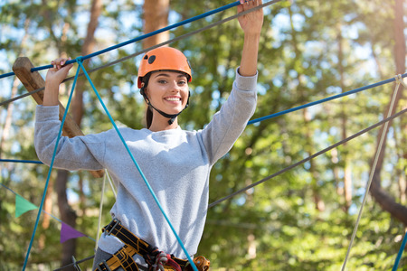 pleasant emotions: Pleasant emotions. Beautiful positive slim woman holding her hands up and touching ropes while taking pleasure in the climb
