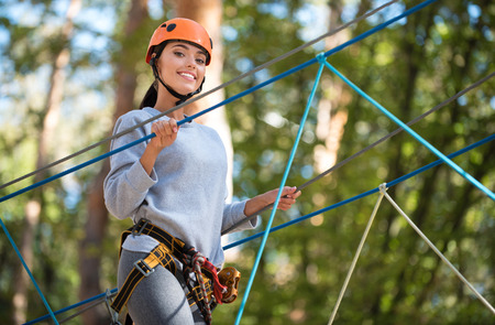 well built: Active weekends. Cheerful well built young woman holding on to the ropes and keeping the balance while enjoying her climbing activities