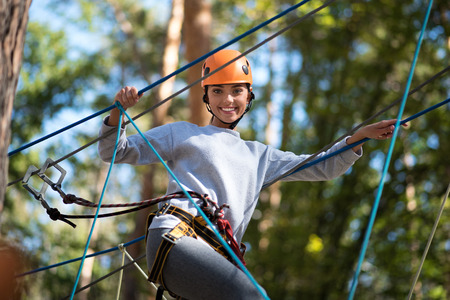 careful: Need to be cautious. Positive confident careful woman wearing a mountaineering helmet and special safety equipment while following the ropes road Stock Photo