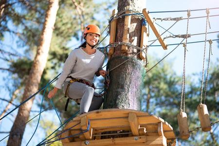 potěšen: Na vysokém lanovém kursu. Šťastná krásná mladá žena sedí u stromu a usmívá se při vysokém lanovém kurzu