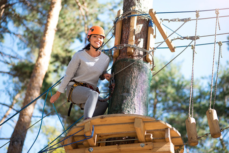 On a high ropes course. Happy beautiful young woman sitting near the tree and smiling while doing a high ropes course