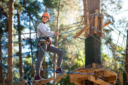 rope ladder: Adventure climbing. Cheerful slim young woman standing on the rope ladder and taking a step while approaching the tree