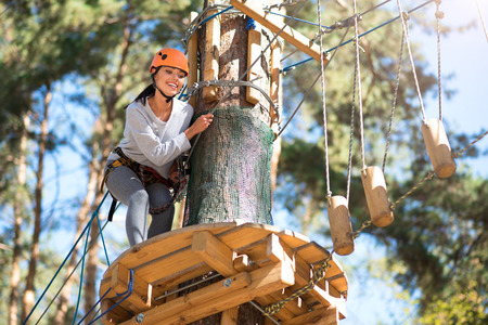 leaning forward: View from the height. Attractive glad slender woman leaning forward and looking down while being high above the ground