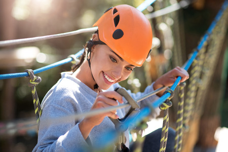 careful: Being cautious. Attractive delighted careful woman holding the mountain carabiner and checking it while thinking about safety
