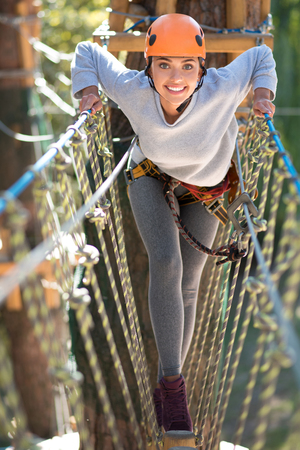 leaning forward: Dangerous activity. Beautiful emotional slender woman leaning forward and moving on a narrow path above the ground while holding the ropes