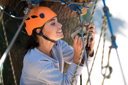 Everything is all right. Beautiful cautious sensible woman holding the mountain carabiner and looking at it while checking the safety equipment Stock Photo