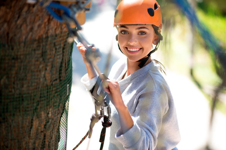 elated: Pleasurable moments. Brave young elated woman holding the ropes and looking at you while climbing in the adventure park