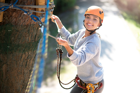 well built: Need to be careful. Attractive emotional well built woman wearing a special outfit and holding on to the ropes while being in the adventure park