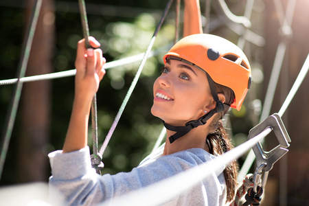 not forget: Do not forget about the safety equipment. Pleasant attractive happy woman wearing a special helmet and looking somewhere up while doing climbing activities