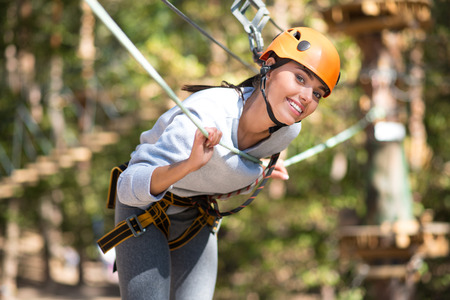 well built: Look at me. Pleasant delighted well built woman leaning forwards and smiling while doing adventure climbing
