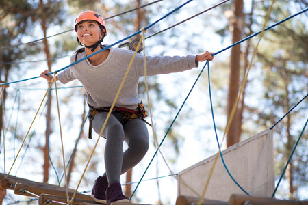 rope ladder: Taking pleasure in the moment. Charming joyful young woman standing on the rope ladder and smiling while enjoying herself Stock Photo