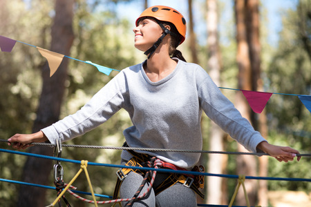 well built: Enjoying the atmosphere. Nice delighted well built woman being high above the ground and looking to the right while doing her high ropes course Stock Photo