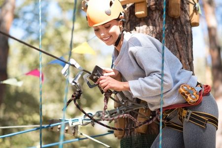 leaning forward: In a special outfit. Cute cheerful slim woman standing in front of the tree and leaning forward while fastening the mountain carabiner
