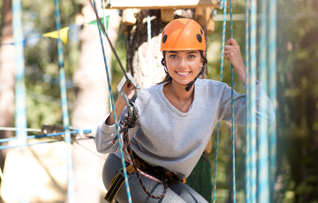well built: Joyful and happy. Attractive pleasant well built woman wearing a mountaineering helmet and wearing special outfit while looking at you