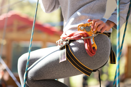 Being precautious. Close up of safety equipment on a young slim woman doing her climbing activities