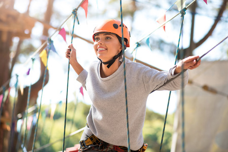 absolute: Absolute happiness. Pleasant beautiful joyful woman smiling and holding on to the ropes while enjoying her time in the rope park