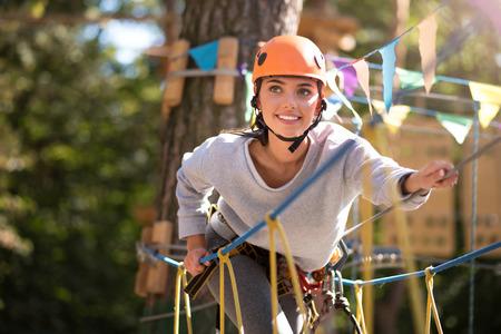 높은 로프 코스. 매력적인 낙관적 인 용감한 여자 앞으로 기울고 및 밧줄 사다리에 등반하는 동안 밧줄을 들고 스톡 콘텐츠