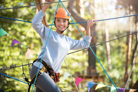Great mood. Happy optimistic slim woman holding on to the ropes and looking at you while spending time in the rope park