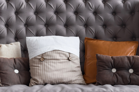 excitation: Soft excitation. Close up portrait of elegant grey couch covered with pillows different size.