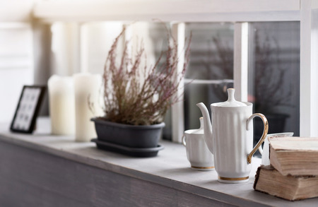 Autumn  is coming.  Close up picture of grey wooden windowsill decorated with white teapot cup, books, flowerpot and candles.