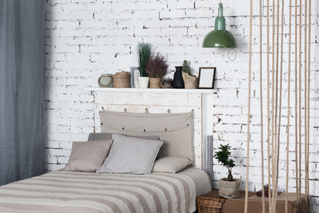All you need. Modern bedroom with big grey bed at on background of white brick wall, above is shelf and next to wicker bedside table.