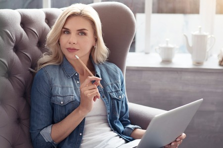 Getting idea. Young thoughtful pretty blond lady sitting on big grey couch with white laptop, and holding pencil on her mouth. Stock Photo