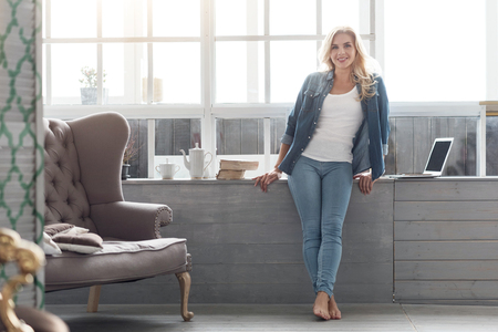 At home. Portrait of happy smiling blond woman standing at big panoramic window barefoot at well-furnished home. Stock Photo