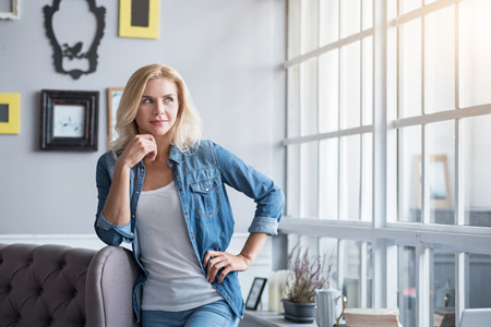 bitchy: Enjoying sunlight. Pretty blond haired woman standing at grey vintage couch and musingly looking aside.