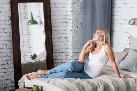 full length mirror: Thought process. Portrait of beautiful blond lady lying on bed barefoot holding her hand at chin and thoughtfully looking up. Stock Photo