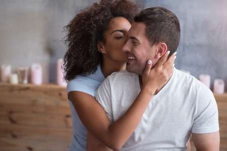 Bedroom tenderness. Happy pretty girl giving a kiss to her delighted husband and spending morning in bed while enjoying the honeymoon. Stock Photo