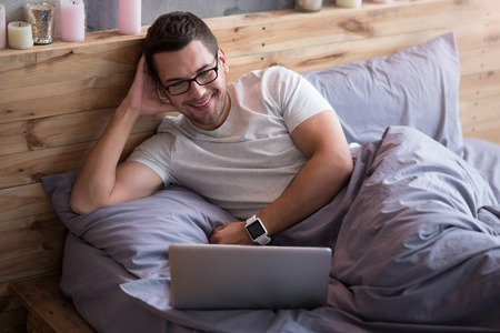 episode: One more episode. Smiling young delighted man lying in a bed and watching tv shows while using his laptop. Stock Photo