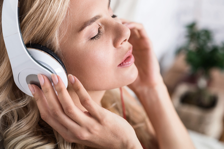 Enjoying moment. Close up of beautiful blond woman listening to music through headphones with closed eyes.