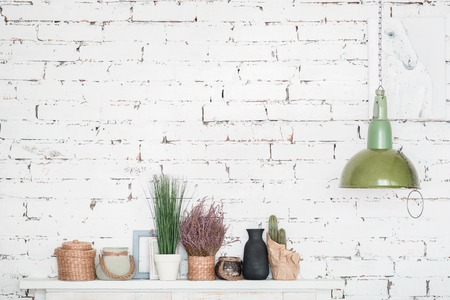 room decoration: Modern design. Nicely decorated white shelf with flowerpots, picture frames and twigged baskets against brick wall.