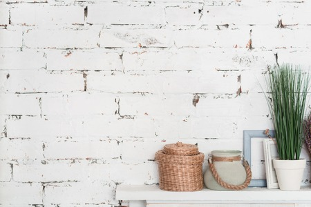 shelf: White on white. Wooden white shelf decorated with flowerpots and picture frames against brick wall. Stock Photo
