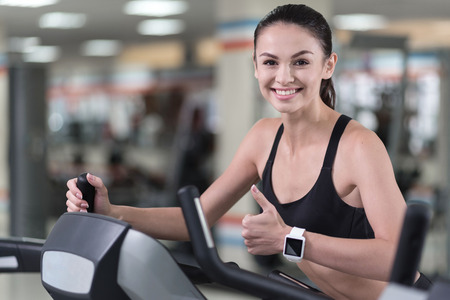 I like it. Happy young pretty woman training in a gym and making an approving gesture with her thumb up while running on a treadmill. Stock Photo