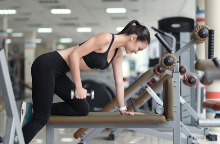 girl working out: Building muscles. Smiling pretty young girl working out using a trainer while spending time in a gym.
