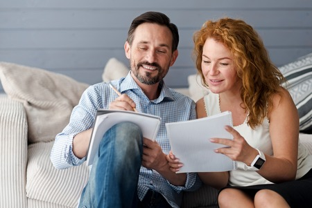 more information: Comparing ideas. Pretty ginger woman leaning to her male partner holding notebook and pencil to get more information.